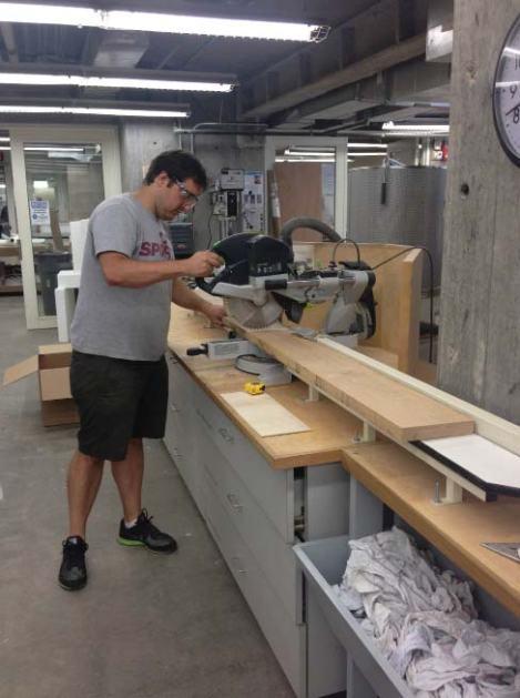 Carmine cutting down wood planks to uniform dimension.