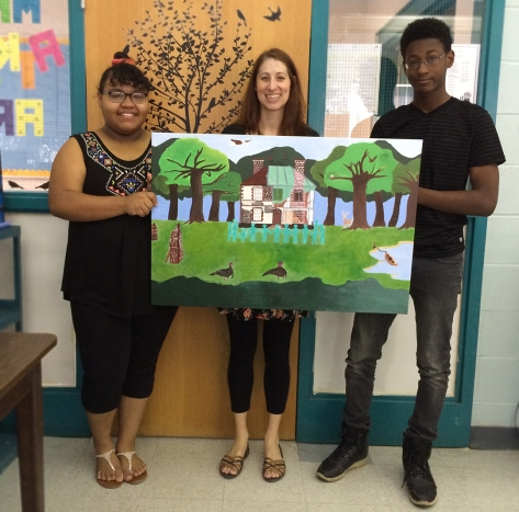 Art teacher Jacy Atkins (center) poses with Vanitra Moran (left) and Avery Chapman (right) with the finished painting.