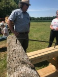 """The Log Dog (wrought iron """"staple"""") bites into the wood of the tree and sawhorse, enabling Craig to turn this log..."""